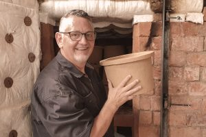 Darrell Nelson steps out of the kiln with a ceramic pot filter in the Clean Water International production facility in Davao City, Philippines