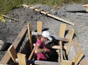 Taya working on the cement and dirt pit latrine using the stabilized soil method.